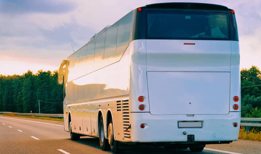 A plain white full size charter bus driving on a road