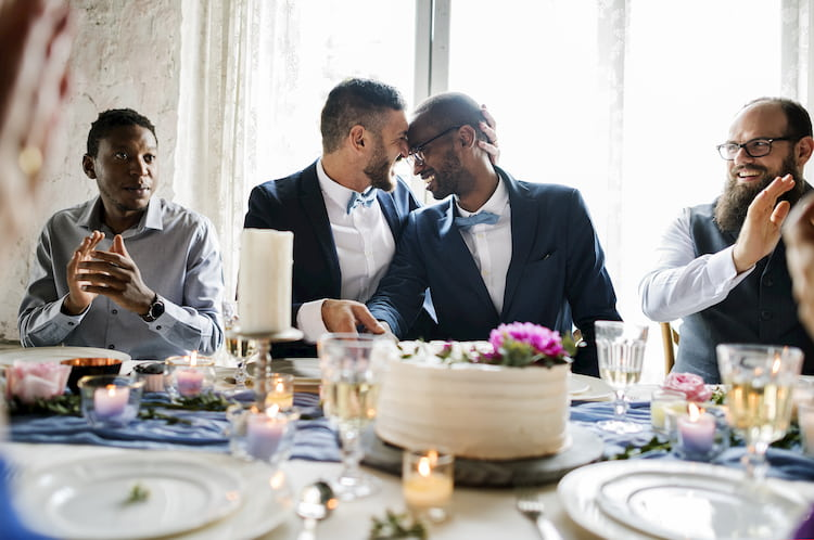 a couple sit at their head table with wedding guests