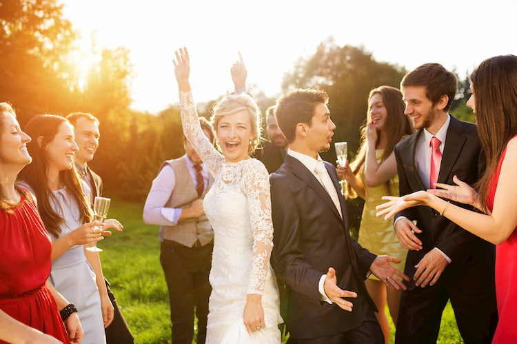 wedding guests dance while the sun sets