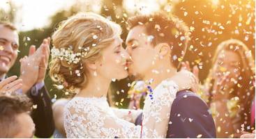 a couple kiss while confetti flies through the air
