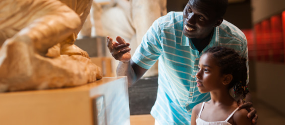 a father and daughter admire a statue in a museum