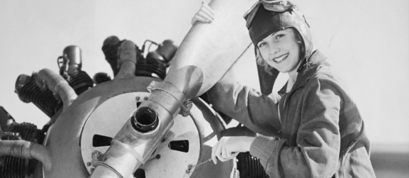 black and white image of a woman in historical pilot clothes, tuning the engine of an airplane