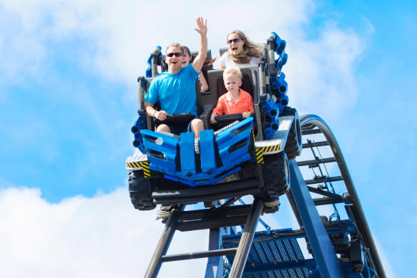 a family on a roller coaster screams as it begins its descent down a big hill