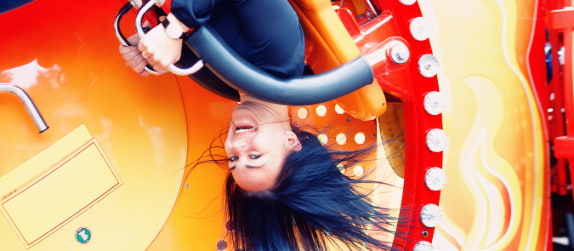a woman screams as a roller coaster flips her upside-down